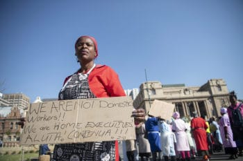 Emma Tshabangu holds up a sign as members of the United Domestic Workers of South Africa (UDWOSA) begin gathering for their protest march at Church Square in Pretoria
