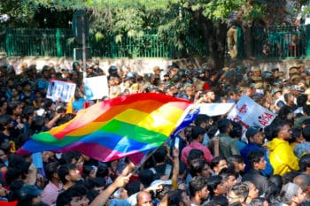Students carry an LGBTQ+ flag at a Fees Must Fall march to the Indian parliament in Delhi
