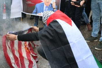 A Palestinian demonstrator burns the American flag in Bethlehem in protest of US President Donald Trump's peace plan. (Photo: Yumna Patel)