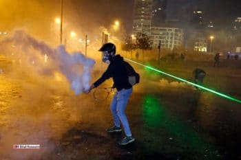 An anti-government protester throwing back a tear gas canister