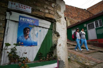 """Neighbors pass by campaign poster of presidential candidate Gustavo Petro at """"Bolivar 83"""" community in the town of Zipaquira, north of Bogota, Colombia, Saturday, June 16, 2018. Petro, a former leftist rebel and ex-Bogota mayor, will face Ivan Duque, a former senator and protege of former President Alvaro Uribe, in a run-off election on Sunday. (AP Photo/Martin Mejia)"""