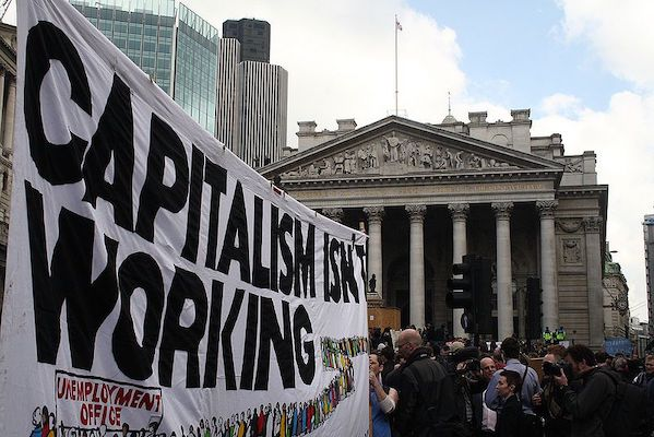 """This article is meant to clarify a point made earlier (Why Didn't Socialism Have Over-Production Crisis, Newsclick, June 30, 2018) about the erstwhile socialist economies not having over-production crises as capitalist economies do. It is in the nature of capitalism to have """"over-production crises"""", i.e., crises arising from """"over-production"""" relative to demand. """"Over-production"""" does not mean that more and more goods keep getting produced relative to demand, so that unsold stocks keep piling up. This may happen only for a brief period in the beginning; but as stocks pile up, production gets curtailed, causing recession and greater unemployment. """"Over-production"""", in short, is ex ante, in the sense that if production were to occur at full capacity use (or at some desired level of capacity utilisation), then the amount produced could not be sold because of a shortage of demand. But it manifests itself in reality in terms of recession and greater unemployment. It is a mistake to believe that such crises are only cyclical in nature, i.e., that they get automatically reversed after a certain period of time. On the contrary, the Great Depression of the 1930s, which was a classic over-production crisis, lasted nearly a decade and was finally overcome because of the war, or, to be precise, because of military expenditure in preparation for the Second World War. Read Also: Why Didn't Socialism Have Over-Production Crises? Since 2008, there has again been an over-production crisis that has persisted with varying intensity right until now. There is, thus, no question of an over-production crisis under capitalism automatically disappearing. But what was striking about the erstwhile socialist economies of the Soviet Union and Eastern Europe is that they were free from over-production crises. The question is why? Over-production crises under capitalism arise because of two main reasons. One, investment decisions under capitalism depend upon the expected growth of demand, for whi"""