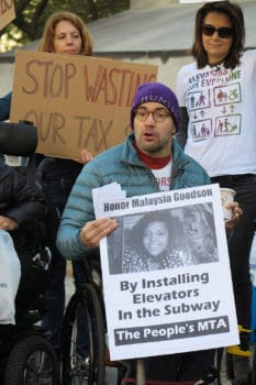 Sasha Blair-Goldensohn, co-founder of Rise and Resist Elevator Action Group, holds up a poster honoring Malaysia Goodson