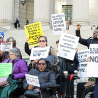 Members of People's MTA; Rise and Resist's Elevator Action Group, Disabled In Action; and the People's Power Assemblies NYC protest at the base of the New York State Supreme Court Building