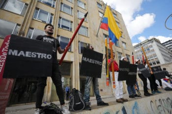 """Anti-government demonstrators hold signs that say """"Teacher"""" in Spanish, during a march in Bogota, Colombia, Wednesday, Dec. 4, 2019. The protester's demands include asking President Ivan Duque to not make changes in the tax, labor and pension laws that are either before the legislature or rumored to be in development. (AP Photo/Fernando Vergara)"""