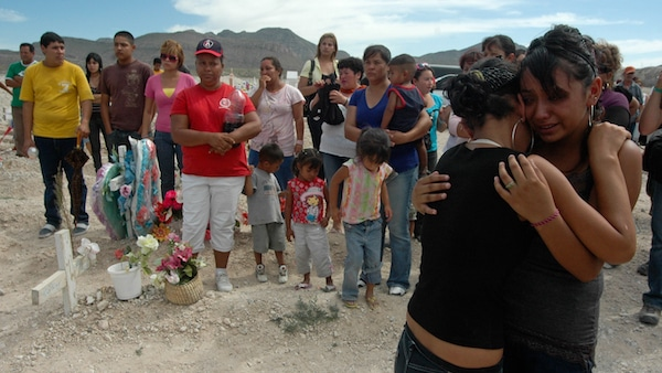 Unidentified people embrace during the funeral of Sergio Adrian Hernandez Huereka, 15, at the cemetery in Ciudad Juarez, Mexico, Thursday June 10, 2010. Mexico condemned the fatal shooting of Hernandez Huereka by a U.S. Border Patrol agent through diplomatic correspondence and some Mexican politicians called for the agent's extradition to face Mexican justice. (AP Photo)