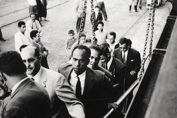 Frantz Fanon walking up a ship gangway. To Fanon's right is Rheda Malek, a journalist from the Algerian National Liberation Front newspaper El Moudjahid. . Frantz Fanon Archives / IMEC