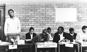 Stephen Biko (standing) at the 1971 conference of the South African Students' Organisation (SASO). The Alan Taylor Residence hall, where the event was held, was the University of Natal's black-only residence for medical students under apartheid. Steve Biko Foundation