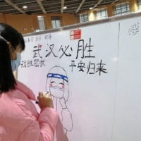 A 10-year-old patient draws on the notice board at a Wuhan hospital every day