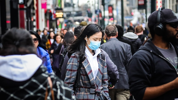 A pedestrian wears a surgical mask on a busy street in mid-town Manhattan, as concerns grow around COVID-19, Tuesday March 3, 2020, in New York. A man from New York City's suburbs was hospitalized in serious condition with COVID-19 on Tuesday, a case that prompted school closings and quarantines for congregants of a now-shuttered synagogue. The state's second confirmed case also raised the possibility that the virus is spreading locally. (AP Photo/Bebeto Matthews)