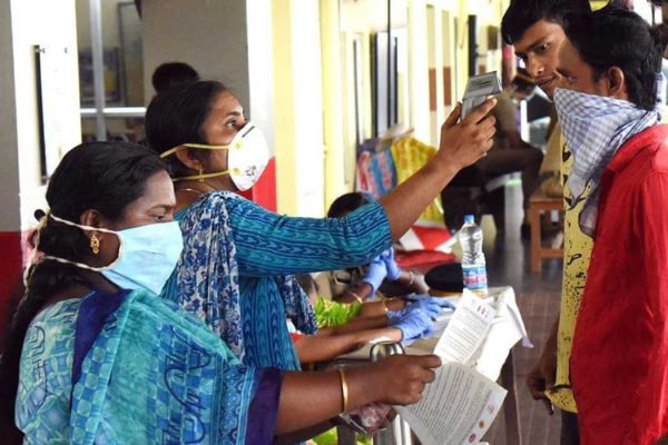 Medical officers measure body temperature of passengers at a railway station in Kochi (state of Kerala) on March 16