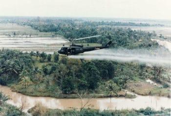 US Army helicopter sprays Agent Orange over Vietnamese fields.