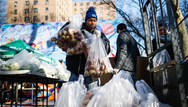 """A volunteer wearing protective gloves organizes pre-bagged food donations at a City Harvest's Bed-Stuy Mobile Market operating in the Tomkins Houses area, Wednesday, March 18, 2020, in New York. Mayor Bill de Blasio said New York City residents should be prepared for the possibility of a """"shelter in place"""" order within days. De Blasio said Tuesday no decision had been made yet, but he wants city and state officials to make a decision within 48 hours given given the fast spread of the coronavirus. (AP Photo/John Minchillo)"""