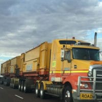 Lone truck on road-train travels down an empty highway