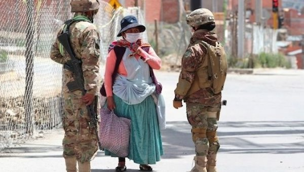 Soldiers question an indigenous woman on the way to buy food. Photo: TeleSUR