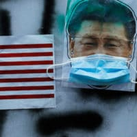 Pictures of U.S. national flag and Chinese President Xi Jinping with mask, made by protestors are displayed in central district of Hong Kong's business district, Oct. 14, 2019. Kin Cheung | AP