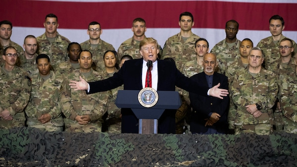 FILE - In this Nov. 28, 2019 file photo, President Donald Trump, center, with Afghan President Ashraf Ghani and Joint Chiefs Chairman Gen. Mark Milley, behind him at right, addresses members of the military during a surprise Thanksgiving Day visit at Bagram Air Field, Afghanistan. President Donald Trump starts the new year knee-deep in daunting foreign policy challenges at the same time he'll have to deal with a likely impeachment trial in the Senate and the demands of a reelection campaign. (AP Photo/Alex Brandon, File)