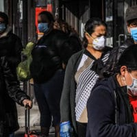 Women in Brooklyn's Sunset Park, a neighborhood with one of the city's largest Mexican and Hispanic community, wear masks to help stop the spread of coronavirus while waiting in line to enter a store, May 5, 2020, in New York. Bebeto Matthews | AP