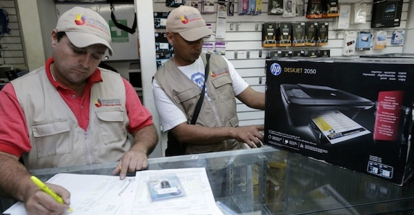 State price checkers inspect a private electronics store. (AVN)