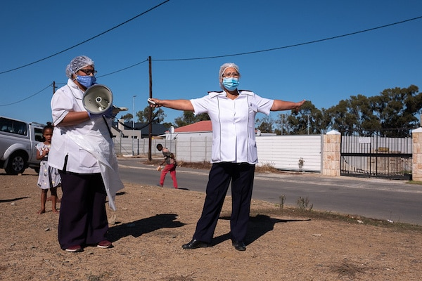 8 May 2020: As part of South Africa's community screening and testing programme, a Khayelitsha Eastern community team tests farm workers in Faure, where a number of positive cases were discovered. A health worker signals what the minimum social distance should be. Barry Christianson / New Frame