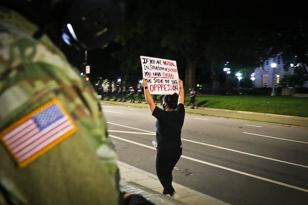 Protester march down the street while Soldiers from the North Carolina Army National Guard 105th Military Police Battalion stand guard in downtown Raleigh, May 31, 2020. Approximately 450 Guardsmen have been mobilized due to civil unrest. The Guard will support local authorities and help safeguard the lives and property of North Carolinians and the ability for individuals to exercise their rights to peaceful protest.