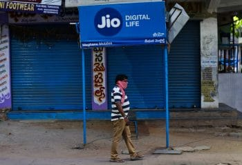A man walks past a Reliance Jio signage in front of a closed shop in Hyderabad, India, Wednesday, April 22, 2020. Facebook says it plans to invest $5.7 billion in India's telecom giant Reliance Jio. The investment will give Facebook a 9.99% stake in Jio Platforms, the digital technologies and app developing division of Reliance Industries. (AP Photo/Mahesh Kumar A.)
