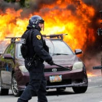 A policeman walks in front of a burning vehicle as protesters demonstrate, May 30, 2020, in Salt Lake City. Rick Bowmer   AP
