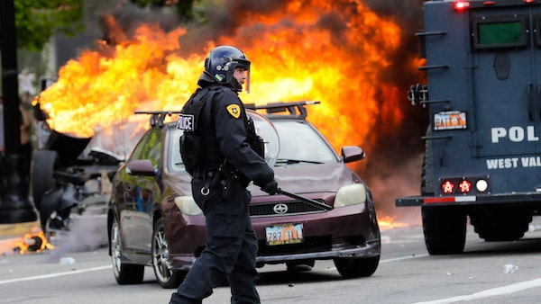 A policeman walks in front of a burning vehicle as protesters demonstrate, May 30, 2020, in Salt Lake City. Rick Bowmer | AP