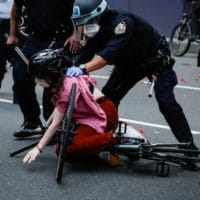 A protester is arrested by NYPD officers for violating curfew beside the iconic Plaza Hotel on 59th Street, Wednesday, June 3, 2020, in the Manhattan borough of New York. Protests continued following the death of George Floyd, who died after being restrained by Minneapolis police officers on Memorial Day. (AP Photo/John Minchillo)
