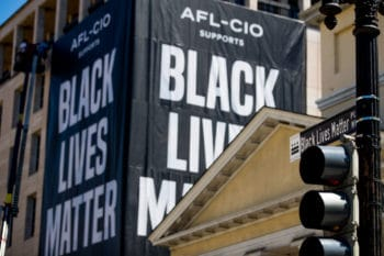 A huge banner is hung from the AFL-CIO building on part of 16th Street renamed Black Lives Matter Plaza in DC, June 12, 2020. Andrew Harnik | AP