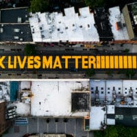 "A giant ""BLACK LIVES MATTER"" sign is painted in orange on Fulton Street, June 15, 2020, in Brooklyn, New York. John Minchillo 