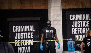 """A DC cop wears a face mask bearing the words, """"I can't breathe… still."""" Photo 