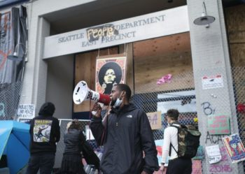 An activist outside the abandoned police station in Seattle's Capitol Hill neighbourhood. Stephen Brashear/EPA