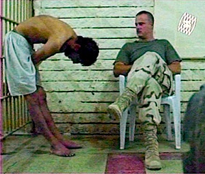 U.S. sergeant interrogates a detainee at Abu Ghraib prison in Iraq who is chained to his cell wall in a distressing position. (U.S. Government)