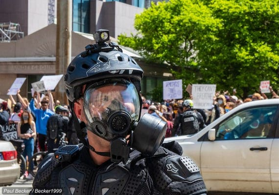 A police officer wears a gas mask at a recent protest over police brutality and racism. Credit: Becker1999 via Flickr. CC BY 2.0.