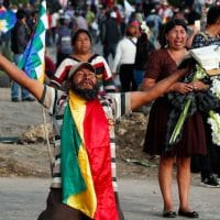 A coca leaf producer kneels holding a bible with his arms outspread asking police to open the way so a march by supports of Evo Morales may continue to Cochabamba, Bolivia, Nov. 16, 2019. Juan Karita | AP