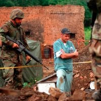US Marines provide security as members of the Royal Canadian Mounted Police Forensics Team investigate a grave site in a village in Kosovo on July 1, 1999