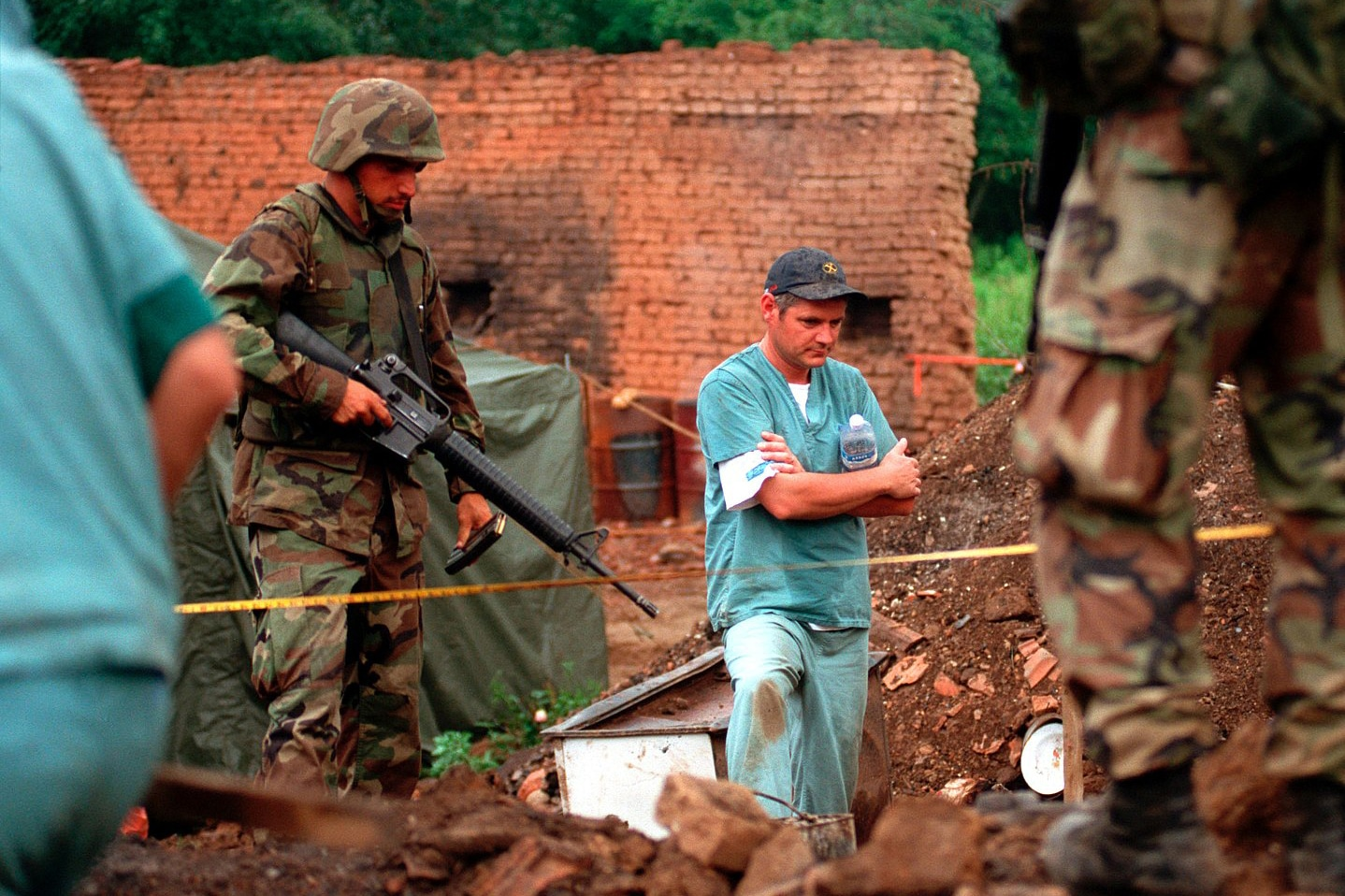 | US Marines provide security as members of the Royal Canadian Mounted Police Forensics Team investigate a grave site in a village in Kosovo on July 1 1999 | MR Online