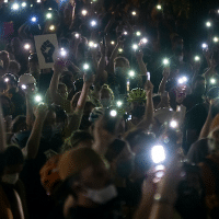 Protesters hold their cellphones in the air during a Black Lives Matter event in front of the Multnomah County Justice Center on July 20, 2020, in Portland, Ore. Photo: Nathan Howard/Getty Images