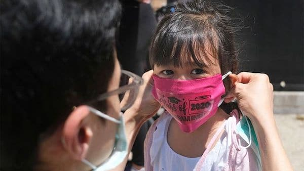 A father helps his child with a mask in front of Bradford School in Jersey City, New Jersey on June 10, 2020 (AP Photo/Seth Wenig, File)