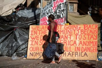 A woman walks with her belongings past a sign as hundreds of people from various African countries are evicted from the makeshift camp they are occupying around the Central Methodist Mission in Cape Town, 1 March 2020 (Photo: Rodger Bosch / AFP / Getty Images)