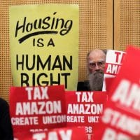 Members of the public look on at a Seattle City Council before the council voted to approve a tax on large businesses such as Amazon and Starbucks to fight homelessness in Seattle. Elaine Thompson | AP