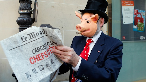 | An activist displays a newspaper headlining the Panama Papers revelations during a banking managers meeting in Paris France Francois Mori | AP | MR Online