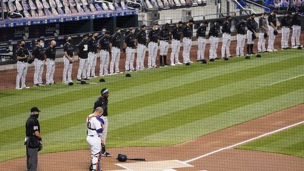 The New York Mets and Miami Marlins stand on the field and bow their heads before a scheduled baseball game ,before walking off in protest, Thursday, Aug. 27, 2020, in New York. (AP Photo/John Minchillo)