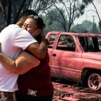 Maria Centeno, right, from Mexico, is consoled by her neighbor Hector Rocha after seeing their destroyed mobile homes at the Talent Mobile Estates, Sept. 10, 2020, in Talent, Ore., after as wildfires devastate the region. Paula Bronstein | AP