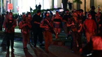 Armed men march in Kenosha. Some of the men pictured are wearing Hawaiian shirts, commonly used to signal association with the boogaloo movement. Photo by REUTERS/Stephen Maturen