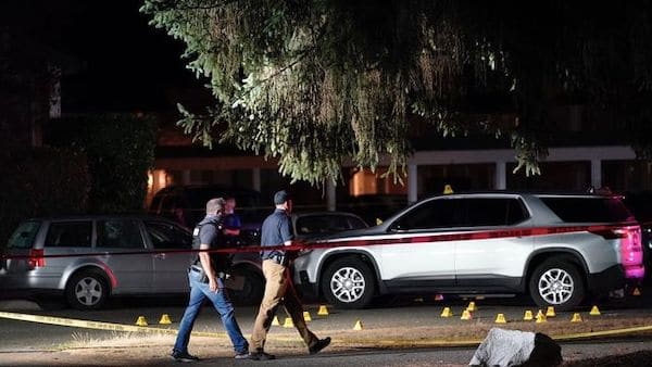 Police walk past evidence markers at a scene Thursday, Sept. 3, in Lacey, Wash., where Michael Reinoehl, 48, was killed by a federal task force. (AP Photo/Ted Warren)