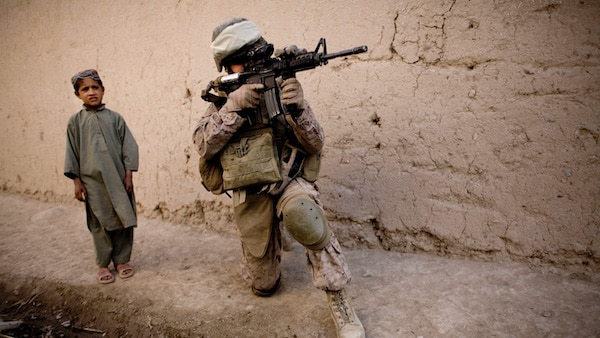 An Afghan boy watches Cpt. Chris Esrey of Havelock, North Carolina, with India, 3rd Battalion 5th Marines, First Marine Division, company, scan the area during a patrol in Sangin, south of Kabul, Afghanistan. Dusan Vranic | AP