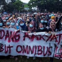"Thousands of Indonesians have taken the streets of Jakarta, Bandung and other cities in protest against the government's push to enact the ""omnibus law""."