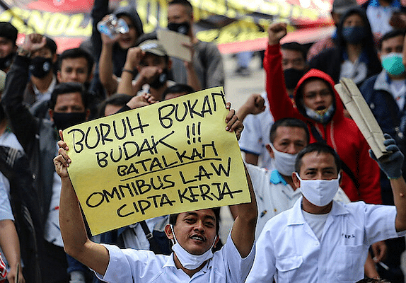 "An Indonesian trade unionist with a sign reading ""Labor is not a slave, cancel the omnibus bill of job creation"" in Jakarta"